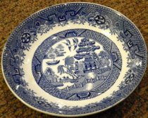 Image of 1999.054.002C - Blue Willow Semi China Finger Bowl, c. 1891-early 1900s  .  Small round white china bowl with a flared raised edge.  Blue design depicts a fence, tree, pagoda, boat and bridge and two outer borders with a geometric motif.