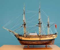 "Image of 2000.008.014 - HMAV Bounty Model Ship by Charles Parsons at 1:48 scale. Wooden ship is a 3 masted square sailing ship, but sails are not up. Each mast has a crow's nest that is flat with a railing towards rear. The deck is a single level.  Rigging is attached with black deadeyes and the rigging forms very intricate netting.  The front of the ship has a figurehead of a female figure wearing a white shirt, red jacket and black hat. There are two black anchors at front of ship, on one each side. The rear of the ship has five 9-pane windows and there are ""bay"" windows on the sides near the rear consisting of three 4-pane windows each.  The port side of the ship is completely finished with a dark wood ""tiled"" bottom while the starboard side is unfinished with the framed ribbing visible in the hull.  There are three dinghies or launches on deck between the two larger masts--two are white and one is brown.  Two cannons are sticking out of windows on each side of the rear (aft) deck.  Above black railing five small hand cannons are mounted on each side.  There is a tiller and a ship's wheel on deck at back of boat.  Model is mounted on a dark stained oak stand which is affixed to a orange painted base with a brown stained bottom.
