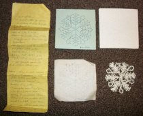 "Image of 2012.001.009 - c. 1978 Snowflake Pattern and Completed Snowflake consists of a yellow, rectangular piece of paper (A) with hand written directions for making a snowflake. The pattern consists of a square, green piece of cardstock (B) with ""Snowflake"" written in the lower right corner, the pattern drawn on it in ink, and holes punched in it. The next part of the pattern is on a square, white piece of graph paper (C) and has ""snowflake"" written in lower right corner, the pattern in pencil with letters A-T written on it, and holes punched into it. There is also a square, white piece of cardstock (D) with just the holes punched into it. Finally, there is a completed snowflake (E) made of white, cotton thread, that measures 3"" in diameter."