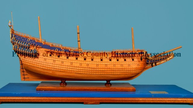 Ship Is Plain Wood With Some Dark Blue And Gold Accents Towards The Rear Front