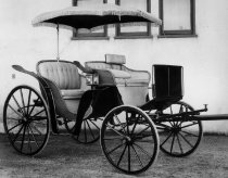 Image of 1973.426 - c. 1890 Four Passenger Park Phaeton.  Could be called a Basket Phaeton, as it is wicker.  Has a fringed parasol top, beige-colored upholstery.  An unusual and rare carriage, since this type of summer vehicle did not usually receive the care that a Brougham or Victoria did, as they were used under different conditions and roads.