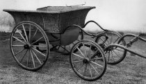 Image of 1973.427 - c. 1890 Governess' Cart.  Because of its wicker body and four wheels, this small vehicle is rare.  A governess' cart usually has two wheels.  Thus, if the horse pulling the cart were to rear, the passengers could be thrown out.  This vehicle is designed so that such an accident cannot happen.  The cart is used to transport children to school and on outings, and is driven by a governess.  Children would occasionally use it for driving ponies.