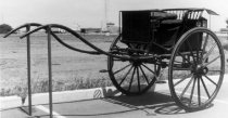 """Image of 1973.429 - c. 1890 Horse Gig has a spindle back rest.  Gig is black with red striping on body and wheels.  Monogramed with """"WPR.""""    Brewster & Co. side lamps.  Fabric cushioned seat covers are maroon in color."""