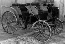 Image of 1975.236.001 - c. 1890 Studebaker Two-seat Park Phaeton.  Two-seat wicker horse carriage has rubber tires and leather fenders; whip pockets and stop plates all intact.  Carriage has black colored upholstered seats.  Seat sides are of natural colored wicker.