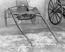 Image of 1975.236.002 - c. 1890 Racing Sulky.  Sulky has inflatable rubber tire and wheels with wire spokes.  Wooden frame is painted red.  A black colored upholstered cushion sits atop the wooden board seat.  Floor for driver's feet is black as is the leather on the sides between the floor and seat.