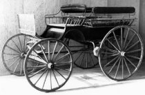 Image of 1975.236.003 - c. 1890 Wagonette Carriage has a two-passenger driver seat with facing side passenger seats in back.  It has iron tires and would be drawn by two horses.  Upholstered seat cushions in back.