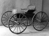 Image of 1975.236.004 - c. 1890 Buggy/Runabout.  Buggy has a single black leather upholstered seat and iron tires.  It would be drawn by a single horse.  Removable black leather cover is affixed with iron side bars.