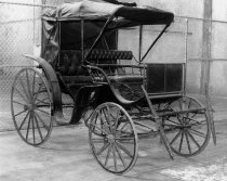 Image of 1975.236.006 - c. 1890 Two-seat Surrey.  Two horse, two seat surrey has iron wheels and a collapsible canopy top.  Bench seats are upholstered black leather.