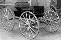 Image of 1975.236.007 - c. 1890 Single-seat Buggy has a bench seat with black leather tufted upholstery stuffed with horse hair.  Wooden body and wheels are painted black and vehicle has rubber tires.