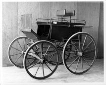 Image of 1975.236.008 - c. 1890 Shooting Trap Carriage.  This is a two-horse drawn carriage.  Metal frame and wheels are painted red.  Body and seat cushions are upholstered in brown-colored leather.  Vehical has white rubber tires and red metal step plates.  There is a wicker boot on the side of carriage.  Possibly used for hunting.