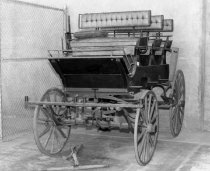 Image of 1975.236.009 - c. 1890 Roofseat Break Carriage.  Three seat (six passenger) two horse-drawn carriage is painted black with a red undercarriage and painted red wheels with iron tires.  It has light running gear, cut under with reach., splinter bar.  Seats are upholstered in brown tufted leather.