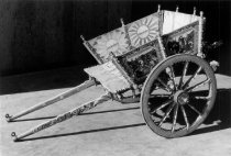 Image of 1975.236.011 - c. 1890 Carretto Siciliano (Sicilian Donkey Cart).  Sicilian pony cart has two wheels.  Wood is highly carved and very ornate.  Underside of carriage is highly decorated hand-painted iron.  Entire cart is painted with figures and images of various colors throughout.