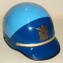 """Image of 2009.004 - San Mateo County Sheriff's Office Riot Helmet (also used in patrol cars before the advent of seatbelts).  Helmet is made of plastic, with black rubber edging along the bottom.  Main body is painted in light blue;  front section and visor is painted in royal blue,  with a band of royal blue extending from visor and along the bottom edge.  Gold-colored plastic trim sits directly above the visor, secured on either end with gold-colored """"buttons.""""  Buttons have a stylized """"P"""" monogram in the center, surrounded by a wreath of flowers.  Directly above the trim is a logo for the San Mateo County Sheriff's Department, a bald eagle with wings spread, sitting on top of a crest with a stylized border.  In the center of the crest is a five-pointed star within a circle.  Surrounding the star are the words """"San Mateo County"""" within a larger circle.  Directly below the crest is the title """"Deputy Sheriff."""" Six plastic circular studs (three on either side) are found along the bottom edge.  Interior is lined with foam, painted in dark gray.  Black leather strapping provides additional cushioning and support for the head.  Strapping is secured with plastic straps that have been inserted into the foam layer.  Chin strap made of synthetic material with black leather protective sleeve attaches to black perforated leather ear flaps.  """"76  /  CANCILLA"""" handwritten in black ink on underside of visor."""