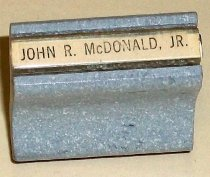 """Image of 2009.006.005 - San Mateo County Sheriff's Office John R. McDonald, Jr. stamp.  Wood-mounted rubber stamp with text that reads, """"JOHN R. McDONALD, JR.""""  Wooden handle is hour-glass in shape and mottled gray and white in color.  Label on handle reads """"JOHN R. McDONALD, JR."""""""