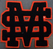 Image of 2010.176.002B - San Mateo High School 'SM' patch, c. 1928-1932.  Black wool yarn patch of the letters 'S' and 'M' superimposed onto an orange felt background.  Secured to cloth backing with adhesive.