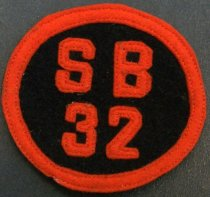 "Image of 2010.176.002E - San Mateo High School 'SB32' patch, c. 1928-1932.  Circular felt patch has orange lettering that reads ""SB  /  32"" and orange trim against a black background.  Lettering and trim are machine-sewn on with orange thread."
