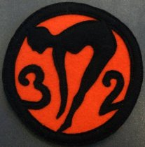 Image of 2010.176.002L - San Mateo High School '32' patch, c. 1928-1932.  Circular felt patch has a black design and trim against orange background.  At center is a profile of a female swimmer or diver.  To the left of this figure is the number '3'; to the right is the number '2'.  Pieces and trim sewn onto background with black thread.