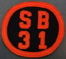 "Image of 2010.176.002M - San Mateo High School 'SB31' patch, c. 1928-1932.  Felt patch has orange lettering ""SB  /  31"" and trim against a black background.  Orange pieces are machine-sewn with orange thread."