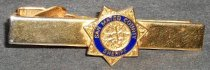"Image of 2012.006.015 - San Mateo County Sheriff's Office tie clip belonging to Gjon T. Pawson, c. 1981-1986.  Brass-plated (?) metal alligator clip has a seven-pointed star with an embossed design in the center.  A blue band with the words ""SAN MATEO COUNTY  /  SHERIFF"" encircles the design."