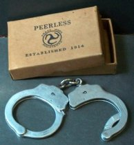 Image of 2012.006.023A-C - Peerless handcuffs(A) in original box(C) with lid(B), c. 1951-2003.  Cuffs (A) are made of aluminum and are connected by a steel chain link.  Single strand of one cuff appears to have been cut off;  remaining portion has two additional sets of deep cut markings.  Accompanied by cardboard manufacturer's box (B & C).