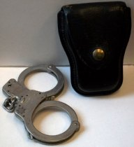 Image of 2012.006.025A-B - San Mateo County Sheriff's Office Smith & Wesson handcuffs (A) and case (B), c. 1981-1986.  Chain link cuffs (A) are made of steel, with both cuffs featuring a single strand of teeth. Black leather case (B) has brass-colored metal snap enclosure and two slots in the back to accommodate a belt.