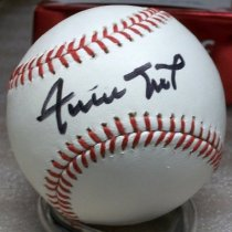"""Image of 2012.023.002A - 2012 Rawlings Baseball Autographed by Willie Mays.  Accompanying letter of authenticity (2012.23.2B) is in the Archives.  This official Major League baseball is comprised of white leather tied with red string and has blue printing throughout.  The Major League baseball logo of a batsman waiting for the oncoming ball is also printed on ball in blue ink.  Willie Mays has autographed the baseball in the """"sweet spot"""" (the narrow unprinted section between threads) with a black Sharpie permanent ink pen."""