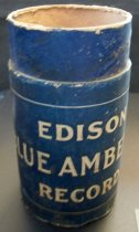 """Image of 2013.036.046 - Edison Blue Amberol Cylinder Case is cylindrical in shape and made of cardboard. The cardboard is colored blue on the outside, while the interior and underside are not colored. The tube is open at the top, and has a sealed base. About an inch down from the top is an outer sleeve that wraps around the main tube. This sleeve reads """"EDISON BLUE AMBEROL RECORD"""" in white lettering  on one side, and has a black and white image of Thomas A. Edison on the opposite side. There is a small pinhole in the center of the base. There is also a circular ring of embossed text around the pinhole, but it is illegible."""