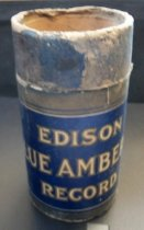 """Image of 2013.036.047 - Edison Blue Amberol Cylinder Case is cylindrical in shape and made of cardboard. The cardboard is colored blue and grey (faded blue?) on the outside, while the interior and underside are not colored. The tube is open at the top, and has a sealed base. The top inch of the case has a band wrapped around it that can be removed. The band sits flush with the outer sleeve. The outer sleeve begins where the band stops (about an inch from the top) and wraps around the main tube. The sleeve reads """"EDISON BLUE AMBEROL RECORD"""" in white lettering with a grey outline on one side, and has a black and white image of Thomas A. Edison on the opposite side. There is a small pinhole in the center of the base. There is also a circular ring of embossed text around the pinhole."""
