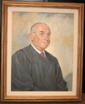 Image of 2014.001.001 - 1986 Portrait of Judge Melvin Cohn by John Bohrer.  Oil on canvas is mounted inside a gold-colored wooden frame with a brown colored outer edge and a white color interior cloth mat. Image is a head and shoulder portrait of former San Mateo County judge Melvin Cohn. He is wearing a black robe over a white shirt with a color and a red tie. He is also wearing eye glasses. His thinning white hair is combed back. Background is comprised of large gold and gray colored brush strokes. He is facing slightly left with his right ear being visible.