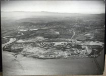 """Image of 2014.014.002 - Aerial View of Foster City. Black and white photographic print on paper mounted to masonite wooden board; pine wooden cleats are mounted to back.  View depicts Foster City under development.  There is water in the foreground and some buildings at lower half of center peninsula and lower right of outer peninsula.  The City of San Mateo can be seen in the background.  In bottom right corner, vehicles are traveling over the SF Bay on Highway 92.  On left at base of slough are the words """"FOSTER CITY"""" in white letters."""