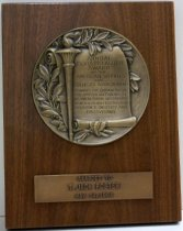 "Image of 2014.014.005 - 1964 Award Plaque Honoring T. Jack Foster. Wooden plaque has a clear varnish and two brass-colored pieces of metal mounted to the front.  The top metal piece is round in shape and has an embossed motif of leaves, a torch and a scroll.  The scroll in inscribed with text that reads, ""ANNUAL  /  HORATIO ALGER  /  AWARD  /  OF THE  /  AMERICAN SCHOOLS  /  AND COLLEGES ASSOCIATION  /  TOWARDS THE ENHANCING OF  /  THE AMERICAN TRADITION  /  OF OVERCOMING OBSTACLES  /  TO ACHIEVE SUCCESS THROUGH  /  DILIGENCE, INDUSTRY AND  /  PERSEVERANCE.""  Bottom metal pieces is rectangular in shape and is embossed with, ""AWARDED TO  /  T. JACK FOSTER  /  MAY 14, 1964."""