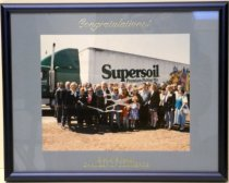 """Image of 2014.017.003 - Stockton Chamber of Commerce at Lathrop Supersoil Plant is a color photograph mounted under glass, beneath a blue mat inside a blue metal  (aluminum) frame. Image depicts a large group of people at a ribbon cutting ceremony, standing in front of a big-rig with a green cab and a white trailer with green type that reads """"Supersoil  /  Premium Potting Mix."""" In the front of the crowd is a man holding large scissors, which have been used to cut a ribbon. Above the image, on the mat and in gold, is """"Congratulations!"""" and on the base of the image, on the mat and in gold, reads """"Greater Stockton  /  CHAMBER OF COMMERCE."""""""