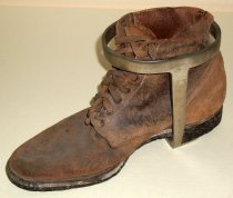 Image of 2014.018.007 - San Mateo County Sheriff's Office braced prisoner or security boot, c. 1920s.  Leather shoe or low-top boot with a steel oval-shaped brace that wraps around the ankle; two steel bars extended from the center of oval to a solid U-shaped steel piece that is secured to the heel of the boot with three screws. Boot is brown in color with fourteen eyes through which a brown cloth lace is tied.  Dark leather sole is both stitched and nailed on. Boot was used for transporting inmates; they were probably chained together at ankles.