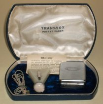 """Image of 2014.018.008 - San Mateo County Sheriff's Office Transvox pocket pager set, c. 1950 to 1970. Set includes a metal pager (A), a triangular-shaped speaker (B), a cord to connect the two (C), a warranty card (D) and a case (E).  Metal pager (A) is rectangular in shape with rounded corners, a hinge at the bottom, a plug outlet at the top right, a plastic dial on the top left and a wire metal clip on back.  On front is inscribed, """"Transvox  /  POCKET PAGER.""""  Speaker (B) appears to be off-white Bakalite plastic, with a rounded, peach-colored tip at bottom of triangle with holes on side for inserting a wire plug.  There is a round, silver-colored piece separating the two pieces of plastic.  There is also a silver-colored metal clip on back.  Cord (C) is comprised of two beige-colored wires twined together with a peach-colored and clear-colored plug at either end.  Warranty card (D) describes the unconditional guarantee and is comprised of black text printed on off-white paper.  Case (E) is rectangular in shape with curved sides and is comprised of a blue vinyl outer shell lined with off-white satin cloth on lid and dark blue velvet on interior base.  Printed in black on underside of lid is, """"TRANSVOX  /  POCKET PAGER."""""""