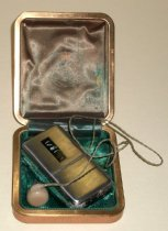 """Image of 2014.018.009A-B - San Mateo County Sheriff's Office Telex pocket pager and case, c. 1960.  San Mateo County Sheriff's Office Telex pocket pager (A) and case (B).  Pocket pager (A) is silver-colored metal (steel?), rectangular in shape with rounded corners.  There is a horizontal hinge halfway down on the front side, allowing the bottom portion to lift open so that a battery can be placed inside.  Interior is beige-colored Bakelite plastic and has makers mark printed in gold.  On the left side is a speaker cord with an earpiece at one end;  plug and outer portion of earpiece are beige-colored Bakelite plastic, while interior portion of earpiece is clear plastic.  At top right of pager is a dial with letters printed in between raised ribs.  On back is a gold-colored metal clip, below which are remnants of a black-colored label with silver writing.  On front lower section is black label tape with raised letters:  """"1R/1.""""  Case (B) has a tan-colored vinyl outer shell.  Interior lid is lined with green satin fabric and has a maker's mark emblem printed in gold.  Interior base is lined with green-colored velvet and has two diagonal raised pieces for holding pager in place.  Case is square in shape with rounded corners, hinged at the back and has brass-colored metal at edges where top and bottom meet."""