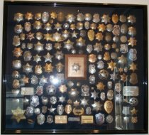"Image of 2014.018.029 - Walter Moore Chief Deputy Sheriff Badge Collection, c. 1941-1960.  Large black box frame lined with navy blue velvet containing at least 120 badges.  Center badge is mounted on a plaque that says, ""Walter Moore  /  in appreciation for services  /  1941 - 1960"" and ""Mounted Patrol  /  San Mateo County"" above and below a silver-colored Mounted Patrol badge.  Outer frame has a black laquer finish."