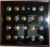 Image of 2014.018.030 - Walter Moore Chief Deputy Sheriff Badge Collection, c. 1941-1960.  Wooden box frame with black velvet lining containing 19 Sheriff's badges, 2 Emergency Ambulance badges and one Commissioner of Human Relations badge.  Wooden frame is wrapped in a faux medium brown stained wood veneer.