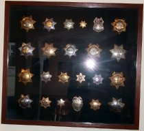 Image of 2014.018.031 - Walter Moore Chief Deputy Sheriff Badge Collection, c. 1941-1960.  Wooden box frame with black velvet lining containing 22 Sheriff badges (including one Matron badge) and one Emergency Ambulance badge.