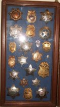 Image of 2014.018.032 - Walter Moore Chief Deputy Sheriff Badge Collection, c. 1941-1954.  Wooden box frame with blue felt lining.  Oak frame has rounded corners and a medium brown finish.  Contains 22 badges including Sheriff's and a variety of police badges.