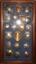 Image of 2014.018.033 - Walter Moore Chief Deputy Sheriff Badge Collection, c. 1941-1954.  Wooden box frame with blue felt lining.  Oak frame has rounded corners and a medium brown finish.  Contains 20 badges including variety of Sheriff, Police, Constable, Ambulance and Army Transport.