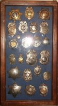Image of 2014.018.034 - Walter Moore Chief Deputy Sheriff Badge Collection, c. 1941-1954.  Wooden box frame with blue felt lining.  Oak frame has rounded corners and a medium brown finish.  Contains 23 various badges including Sheriff, Police, Texas Ranger, Special Patrolman and Internal Revenue Service.