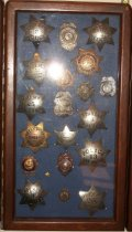 Image of 2014.018.036 - Walter Moore Chief Deputy Sheriff Badge Collection, c. 1941-1954.  Wooden box frame with blue felt lining.  Oak frame has rounded corners and a medium brown finish.  Contains 20 various badges including Sheriff, Police and Constable.