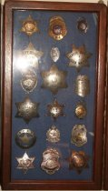 Image of 2014.018.037 - Walter Moore Chief Deputy Sheriff Badge Collection, c. 1941-1954.  Wooden box frame with blue felt lining.  Oak frame has rounded corners and a medium brown finish.  Contains 21 various badges including Sheriff, Police, Traffic Officer, Fire Department and Marshal.