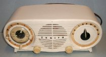 """Image of 2014.021.001 - Zenith """"Owl Eyes"""" Clock Radio, 1950, is oval in shape with flat top, front and back and curved sides.  """"Legs"""" flare out from bottom of oval at both ends.  Plastic clock is off-white in color.  """"ZENITH"""" is printed in black letters through center of round speaker which has horizontal slats and is located in the front center of clock.  There are two round sections, similar in size, on both sides of the speaker.  Both have gold-colored outer borders.  The one on the left is the clock and has the numbers 1-12 encircling within the gold border with the exception of 3, 6 and 9; in place of these numbers are small plastic off-white knobs for controlling the alarm and sleep settings.  Clock hands, second hand, and text describing alarm and sleep settings are all in the center of outer circle under a round bulbous piece of glass.  Clock hands are painted with a glow-in-the-dark finish.  Round section on front right is the radio dial and has numbers 5.5, 6, 7, 8, 9, 10.5, 12, 14 and 16 printed at top within the gold border.  In center is a black plastic dial with a white stripe that is controlled by a gold-colored plastic knob located at bottom front between speaker and radio section.  A second gold-colored plastic knob is located at bottom front between the clock and the speaker and controls volume.  Unit has a brown colored electrical cord and a Masonite back with numerous cut-outs for ventilation.  Cut-out at bottom, just left of center, has an electrical outlet for powering other appliances not over 1100 watts.  Round opening at back right has a metal dial for setting the time on the clock.  Paper instructions and specs are mounted to underside of clock."""