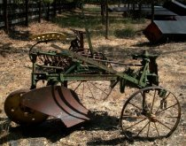 Image of RF2012.003 - John Deer sulky plow is solid iron with a painted green body and painted yellow seat and wheels.  There is a large spoked wheel on left side, a smaller spoked whell at front right and a solid wheel at back just behind blade.  Seat is spade-shaped and is outlined with two rows of perforated holes.  There is a long leer on right and left sides and a smaller kick-lever in center.  Springs accompany various beams of body.