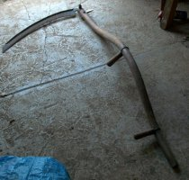 Image of RF2014.003 - Scythe has a serpentine wooden handle with two wooden side-grips affixed with metal brackets.  Curved blade is bolted to top of handle.