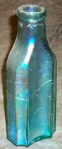 Image of 1999.048.047 - Condiment bottle recovered from City Centre Plaza, c. 1860-1880. The 8-sided bottles have wide, concave front and back panels with flat narrow side panels bound together by relatively wide, concavely beveled corners. The rim was ground down flat and double ring finish and shows evidence of glass machine manufacture.  A 1.25 inches short narrow neck flares out 1.375 shoulders to a 4. inches cylindrical body. The bottle is shaped like an oblong octagon at base.
