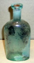 Image of 1999.048.094 - Medicine Bottle recovered from City Centre Plaza, c. 1880-1920. This bottle is oval shaped with a flat front face in cross section and it has narrowed slightly from shoulder to base. The rim has prescription finish which is narrow (vertically) and the outside surface distinctly tapers in from the top surface of the finish to bottom. A cork stopper closed the mouth of bottle. A 1.125 inch short and narrow neck flares out 1 inche shoulders to a 4.5 inch body. The base is shaped like oval with a slightly concave circle. The bottle is clear and has a green tint and shows evidence of glass machine manufacture.