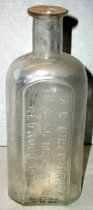 Image of 1999.048.108 - A.R.Kirkpatrick Medicine Bottle recovered from City Centre Plaza, c. 1870-1920. This bottle is oval shaped with a flat front face in cross section and it has narrowed slightly from shoulder to base. The rim has prescription finish which is narrow (vertically) and the outside surface distinctly tapers in from the top surface of the finish to bottom. The front side of bottle is embossed vertically (in a plate) with A.K. KIRKPATRICK/ PIONEER DRUG STORE/REDWOOD CITY. A 1.125 inch short and narrow neck flares out .75 inches shoulders to a 4 inch body. The bottle is clear and shows evidence of glass machine manufacture
