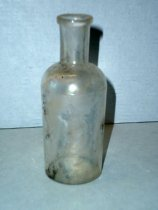 Image of 1999.048.141 - Medicine Bottle recovered from City Centre Plaza, c. 1830-1920. This bottle is round shaped.  The rim has prescription finish which is narrow (vertically) and the outside surface distinctly tapers in from the top surface of the finish to bottom. A .875 inch short and narrow neck flares out 75. inche shoulders to a 2.375 inch body. The bottle is clear and shows evidence of glass machine manufacture.